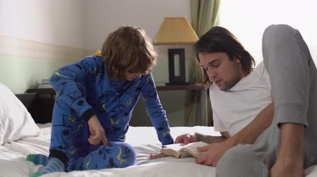 понимание : Two brothers lie down in bed, older handsome brother read for small cute brother a book.