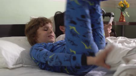 juntar : Two brothers lie down in bed covered white blanket, then cute kid stand up and start to dance on the bed.