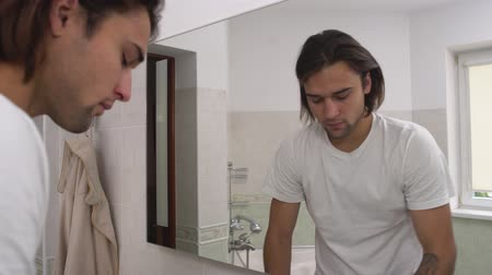 coming home : Young handsome cute man with long brown hair coming in the bathroom and brush his teeth while looking in the mirror. Stock Footage