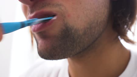 escovação : Mans face brushing his teeth with blue toothbrush in white background.