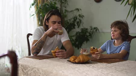 toalha de mesa : Two handsome brothers sitting in kitchen table and eating croissant with cappuccino.
