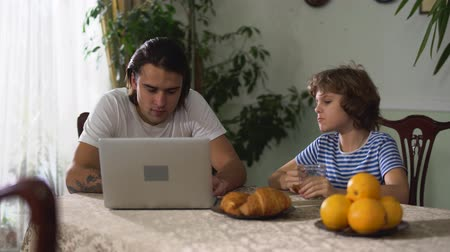 megjegyzés : Small cute boy sitting on the kitchen table eating croissant with cappuccino and older adult handsome brother watching laptop. Kid discuss with brother topic in computer. Stock mozgókép