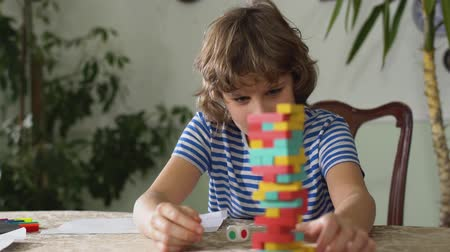 compreensão : Small adorable cute kid sitting on the table and play interesting game inside house.