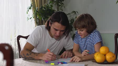 compreensão : Two brothers, one handsome adult and one cute small boy, sit on the table and handsome man draw picture in the paper with colors pencils.
