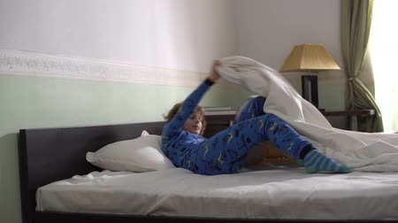 pizsama : Small cute adorable boy running inside the bedroom and jumping fast in bed pretend like he is sleeping.