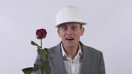 propor : Young man in construction white hat and classical suite give a long red rose in white background. Vídeos
