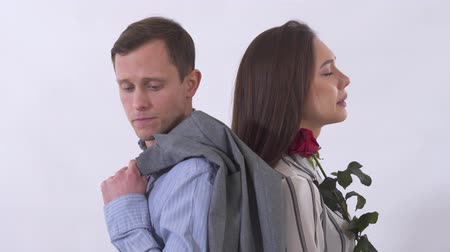 cant : Portrait ofman and woman having a quarrel close up. Couple standing with back to each other. Lady is holding rose and crying, gentleman tries to look at her can not stand her tears. Shooting in the studio on a white background Stock Footage