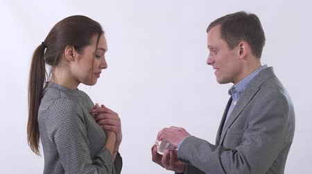 expectativa : Portrait of genuine man in gray suit gives small box to woman close up. Man makes marriage proposal to lady. Woman is happy, she agree to marry the man. Shooting in the studio on a white background