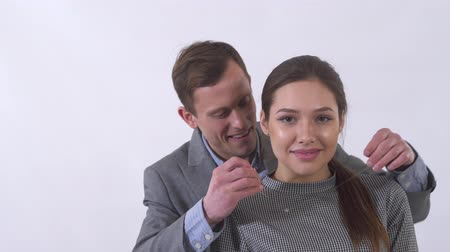 кулон : Portrait of genuine man in gray suit puts a pendant on the neck of a girl close up. Woman is happy because of a gift. Emotional young woman receive present from her boyfriend. Shooting in the studio on a white background Стоковые видеозаписи