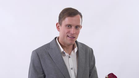 nerd : Portrait of genuine self-confident man in suit extends a hand forward holding red rose close up. Gentleman is flirting on camera. Shooting in the studio on a white background