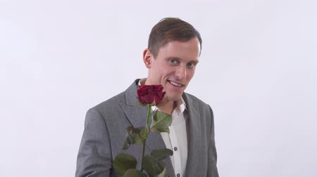 привлекать : Portrait of genuine self-confident man in suit extends a hand forward holding red rose close up. Gentleman is flirting on camera. Shooting in the studio on a white background