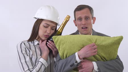 champagne bottles : Portrait of crazy couple close up. Man holds green pillow, woman in builders helmet champagne bottle. Lady pretending to sleep, then wakes up. Shooting in the studio on a white background Stock Footage