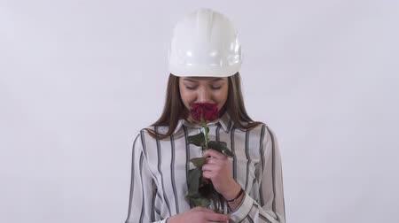 tebrik etmek : Young beautiful woman in construction white hat holding a red rose in her hands and very happy smelling flower.