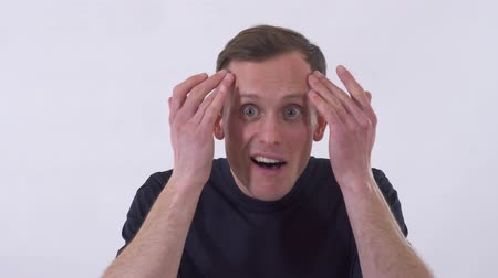 ouvir : Funny young man make weird faces. Shooting on a white background. Stock Footage