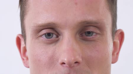 gözler : Close up face of man looking in camera. Man is depressed, disappointed his face shows hidden emotions. Shooting in the studio on a white background. Stok Video