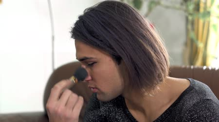 nőiesség : Portrait of handsome man doing makeup close up. Adult transvestite man applies blush with makeup brush on his face. Concept of femininity in a man