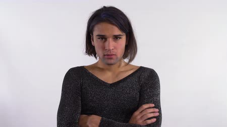furrow : Portrait of handsome man with makeup standing in profile looking at camera with furrowed eyebrows, then turns and rubs his face with palms looking at camera. Cute transgender man in the studio