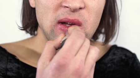 minoria : Lower jaw of handsome man with long hair applying lipstick on his lips in the studio. Transgender man in black dress does makeup on white background. Concept of femininity in a man