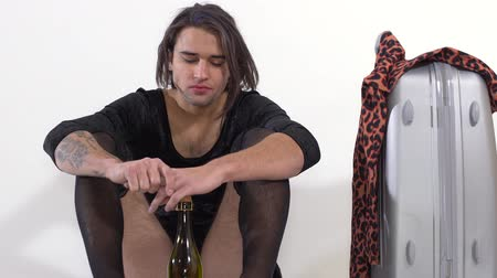 arrasto : Handsome man with stockings on legs and tattoo on hand sitting on the floor with bottle of wine and crying. Travel bag standing near. Transgender man is sad and depressed