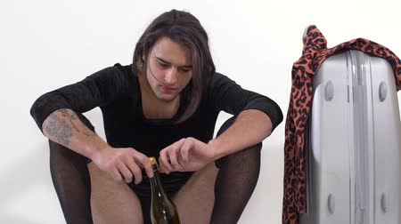 arrasto : Handsome man with black stockings on legs and tattoo on hand sitting on the floor with bottle of wine and crying looking down. Transgender man is depressed