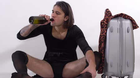 arrasto : Handsome man with stockings on legs and tattoo on hand sitting on the floor crying. Transgender man spits out a cigarette, then drinks wine from bottle. Travel bag standing near. Man is sad and depressed Vídeos