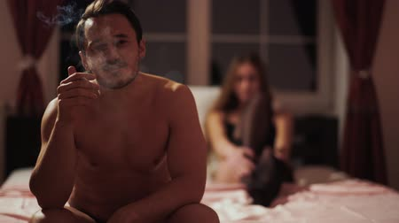 üstsüz : Young happy guy smokes sitting on the bed and against the background of a beautiful young girl in stockings