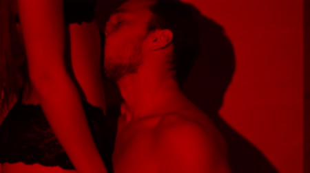 külot : Passionate athletic man kissing belly of woman close up in slow motion. Lovers have foreplay in red light. Beautiful couple making love in private place Stok Video