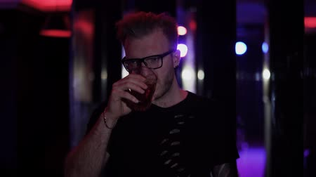 가는 사람 : Portrait of relaxed man standing with glass of alcohol at the disco close up. Adult man in glasses looking at camera drinking his cocktail. Leisure of party-goer