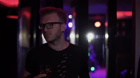 серьги : Portrait of relaxed man standing with glass of alcohol at the disco close up. Adult man in glasses looking at camera drinking his cocktail. Leisure of party-goer
