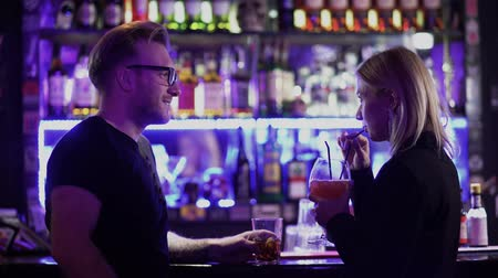 concentrar : Handsome bearded guy and pretty young woman with blond hair standing near a bar counter in a nightclub. A man and a girl drinking a delicious alcoholic cocktail look at each other. Holiday party people.
