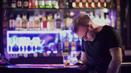brincos : Attractive bearded man with glasses texting on his cell phone while standing at the bar counter