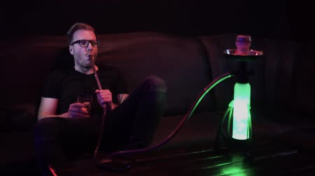 никотин : Adult man in glasses exhales steam in night club sitting on leather couch. Man smoking hookah in modern bar. Hookah mine glows in different colors. Leisure of party-goer.