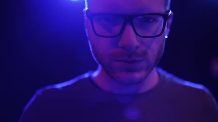 хулиган : Portrait of creepy adult man in glasses looking in camera close up. Face of strange man standing with flashing colored lights on the background Стоковые видеозаписи