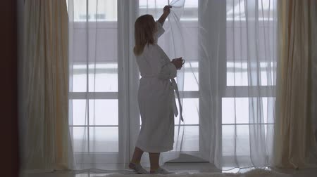 happy socks : Plump girl in white long bathrobe walks to large floor-to-ceiling window with cup of coffee or tea. Lady straightening the tulle. Morning of happy young chubby woman