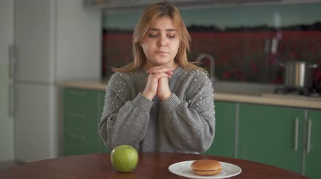 baixo teor de gordura : Portrait of thoughtful chubby woman alternately looking at the burger and big green apple in the kitchen. Difficult choice between healthy and unhealthy food. Concept of diet of plump person