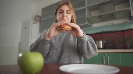 choise : Close up apple and burger lying in front of chubby girl. Young woman takes hamburger first, but puts it pack on the plate and takes apple. Difficult choise between healthy and unhealthy food. Concept of diet of pluml person