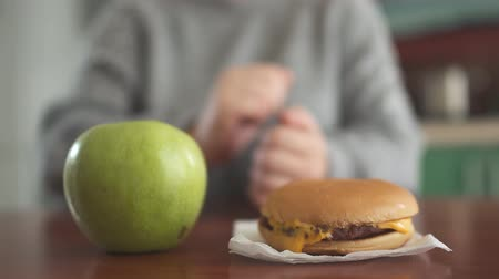 baixo teor de gordura : Close up apple and burger lying in front of blurred figure of unrecognizable chubby girl. Hand of woman wants to take hamburger first, but takes apple. Difficult choise between healthy and unhealthy food