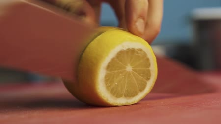 cítrico : Hands of cook slicing lemon with a big chef knife close up. Healthy food preparation in modern restaurant
