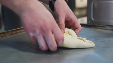 baking dishes : Hand of man working with dough close up. Chef preparing Ajarian khachapuri Georgian cheese pie with egg. Tasty dish making in cafe. Georgian cuisine