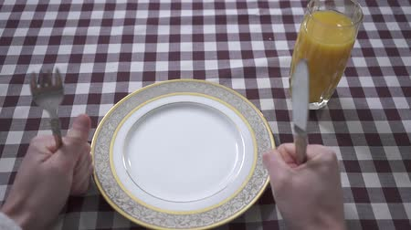 masa örtüsü : Mans hand knocking on the table with his fists, demanding food, holding fork and knife close up. Empty plate and orange juice glass on the table with checkered tablecloth. Fried egg falls on the plate. Breakfast of the man. Concept of feeding. First perso