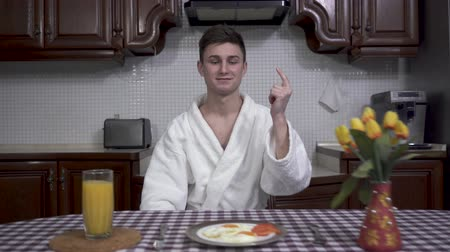 miraculous : Confident smiling man in white bathrobe snapps his fingers and table with breakfast appears in front of him. Plate with fried eggs, orange juice and vase with tulips are on the table covered with checkered tablecloth Stock Footage