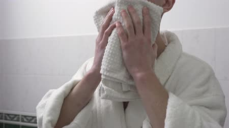 olhando para cima : Confident man in white bathrobe wipes his face with a towel looking in the mirror in the bathroom. Morning time of young man. Preparing for the new day. Camera moves up