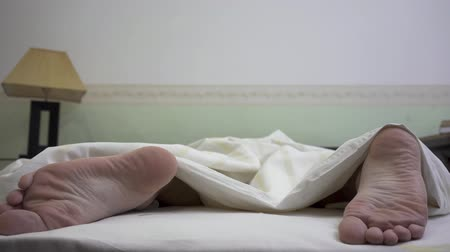 acalmar : Bare feet men sticking out from under the blanket close up. The man tossing and turning in his sleep. Morning time of young man human Stock Footage