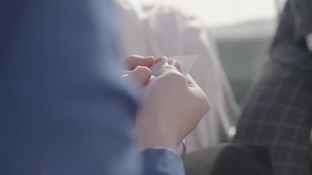marker : Mans and womans hands hide small paper in them hands and write letter M on it, woman also hold metal hearts in hands and body of a man in classical suit sit next to this couple. Stock Footage