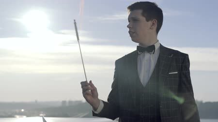 fire suit : Young illusionist showing interesting magic trick with stick in fire and then turn it into metal cane. On background is blue amazing sky, sun and sity from the top view.