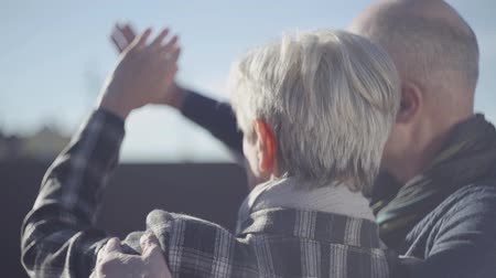 strong granny : Back of woman with grey short hair and back of bald old man standing outside and close with hands a face from the strong sun Stock Footage