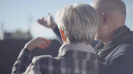 strong granny : Rear view of an elderly couple looking at the sky and communicating with each other. Mature married couple outdoors.