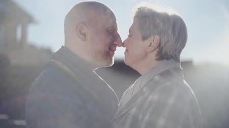 čelo : Happy senior couple look at each other, touching noses and old bald man kiss womans forehead with love, passion and admiration. Amazing happy family.