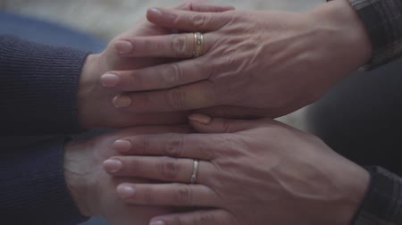 patting : Senior mans hands reaching out. Womans putting her hands in males hands. Hands with wedding rings.