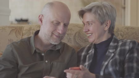 запомнить : Adult couple sitting on the big sofa and bald woman showing photos in the mobile phone for his old man with short grey hair. Family are happy and smiley looking at each other with love and tenderness.